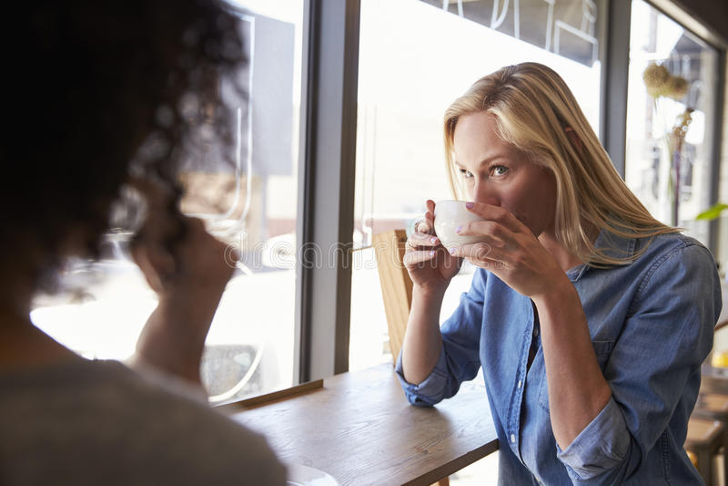 见面在咖啡店的两个女性朋友 免版税库存照片