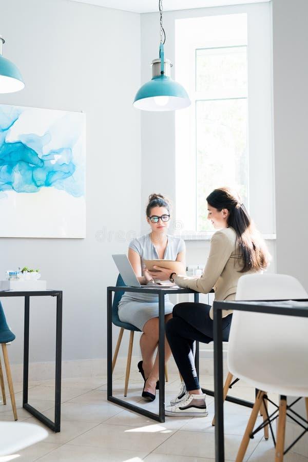 见面在咖啡馆的两名女实业家 免版税库存照片
