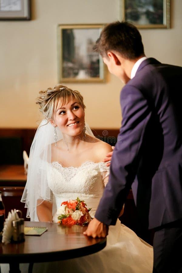 见面在咖啡馆的新婚佳偶,人要求坐在桌上的妇女,表示兴趣,提案 免版税库存图片