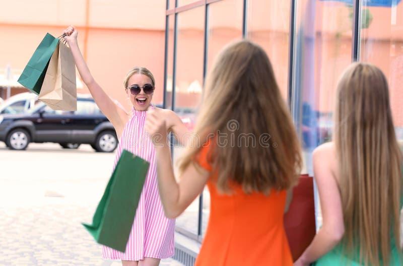 见面在城市街道上的商店附近的愉快的年轻女人 免版税库存照片