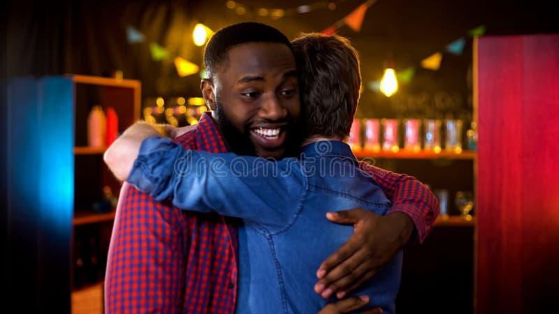 见面在客栈和拥抱的学院伙计,招呼姿态,友谊 库存图片