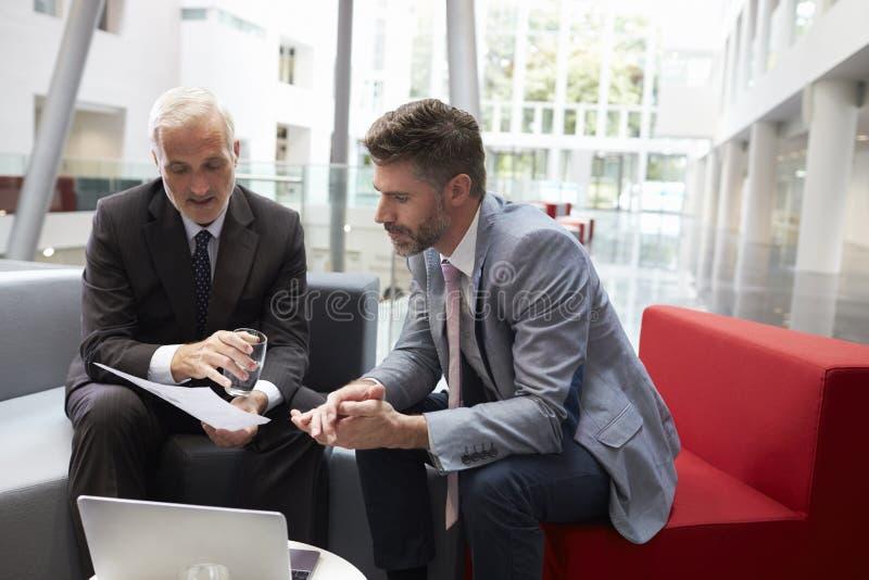 见面在现代办公室大厅地区的两个商人  免版税图库摄影