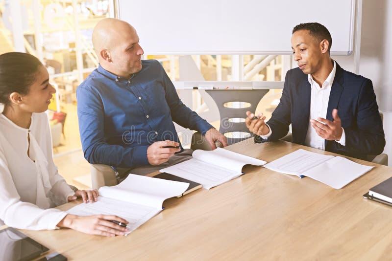 见面在现代办公室空间的三个折衷企业个体之间 库存照片