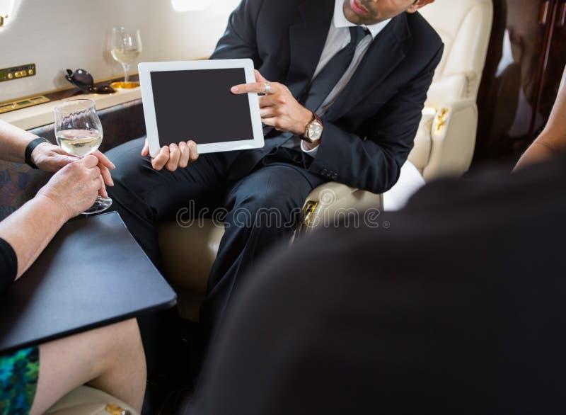 见面在私人喷气式飞机的商务伙伴 免版税库存照片