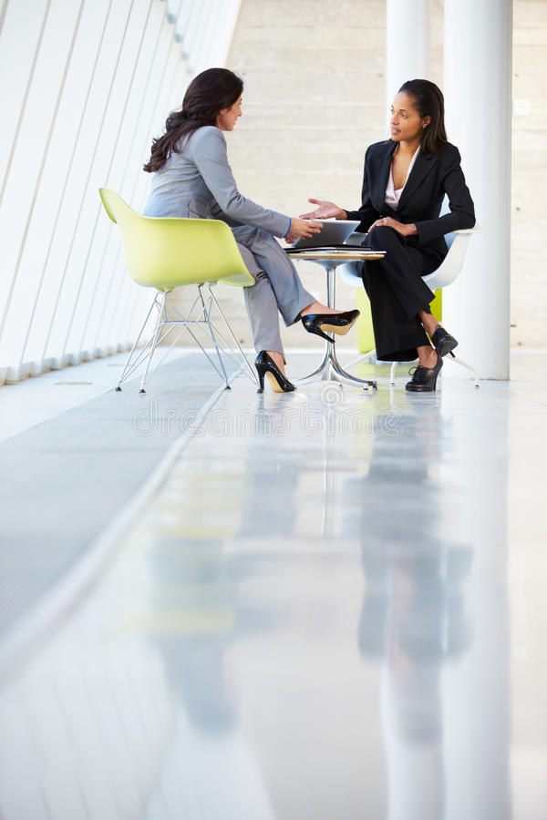 见面在表附近的二名女实业家在现代办公室 免版税图库摄影
