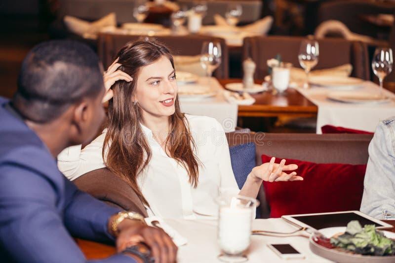 见面在餐馆的小组青年人在晚餐 免版税库存照片