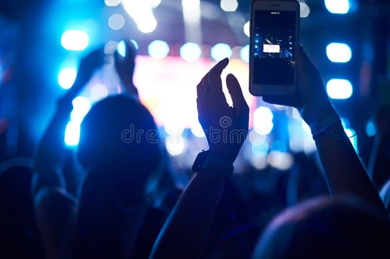 观众人群用使用照相机电话的手采取图片和录影在生活音乐会,智能手机记录实况音乐festiva 免版税库存图片