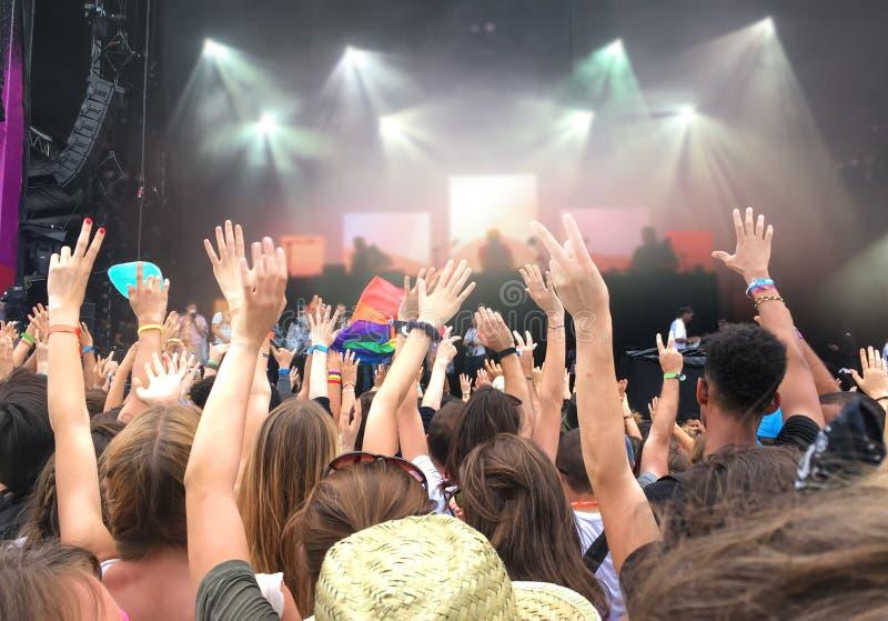 观众用手被举在音乐节,被弄脏的阶段在背景中点燃 免版税库存图片