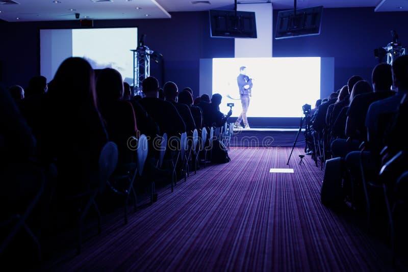 观众背面图在有在阶段、事务和教育的报告人的会场或研讨会会议 免版税库存照片