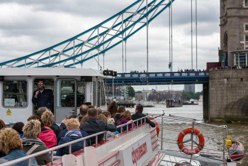观光的小船的游人在塔桥梁附近在伦敦, Englan 免版税库存照片