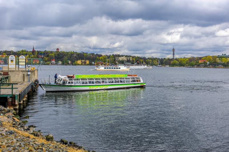 观光的小船进行中在Masthamnen轮渡码头附近在斯德哥尔摩港口,在一个晴朗的春日 r 库存图片