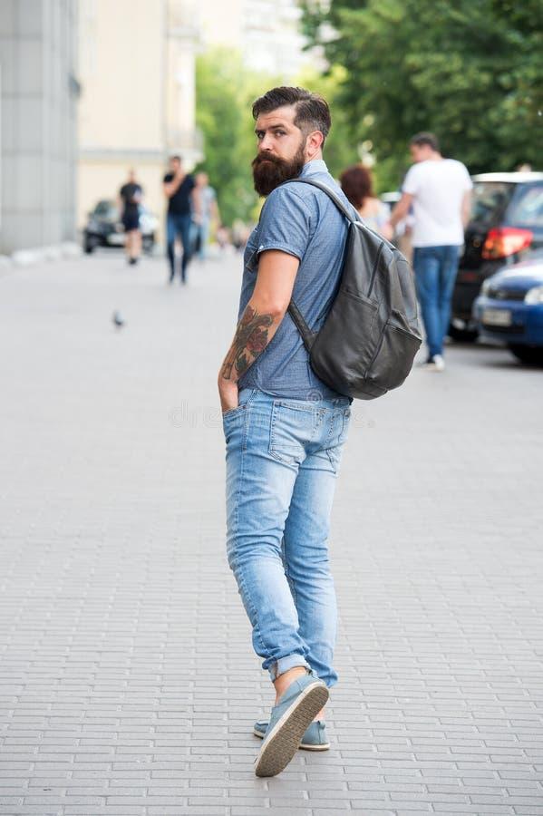 ?? 观光的概念 都市旅行的背包 行家佩带的背包都市街道背景 库存图片