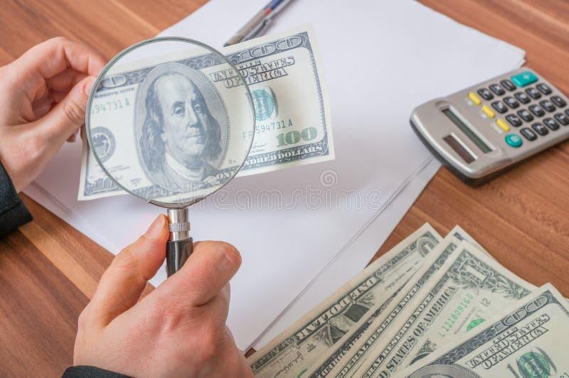 观察伪造品或假劣美元钞票与放大镜 库存图片