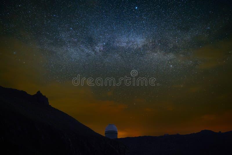 观察在晚上满天星斗的天空 探险空间的观测所在明亮的银河的背景 免版税图库摄影