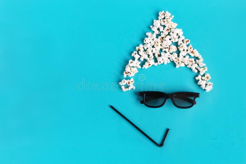 观察者,3D玻璃,玉米花的抽象乐趣图象 在蓝纸背景的戏院时间 概念戏院电影和娱乐 免版税库存图片
