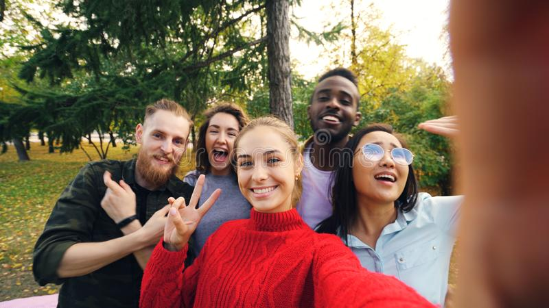 观点射击了少妇有照相机的保存设备和与朋友不同种族的小组的采取selfie在公园 免版税库存照片