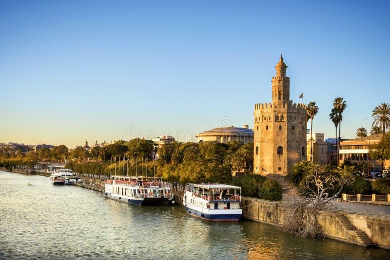观点的金黄Tower Torre del塞维利亚,安大路西亚,在河瓜达尔基维尔河的西班牙Oro日落的 库存图片