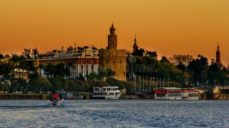 观点的金黄Tower Torre del塞维利亚,安大路西亚,在河瓜达尔基维尔河的西班牙Oro日落的 免版税库存照片