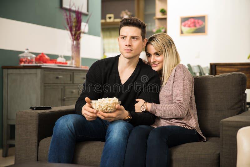 观看一部可怕电影的逗人喜爱的夫妇 免版税库存照片