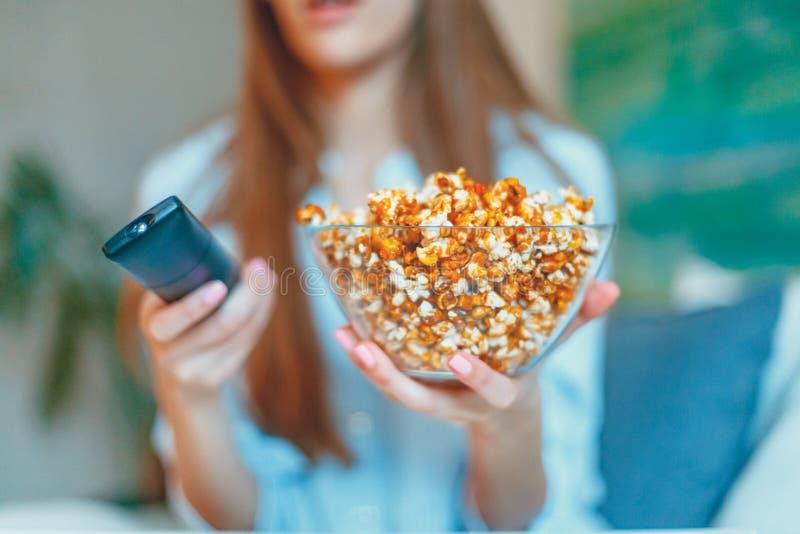 观看一部电影和吃玉米花的美丽的年轻微笑的妇女在床上 免版税库存照片