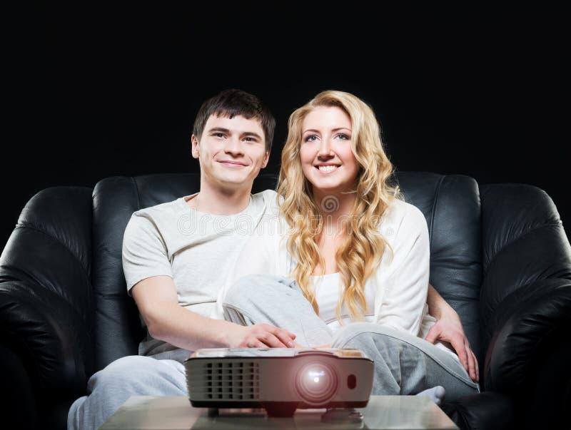 观看一部电影或体育广播在激光放映机的年轻家庭 图库摄影
