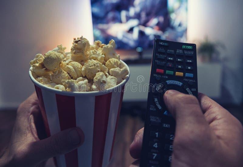 观看一部电影的年轻人在他的客厅用玉米花和r 库存照片