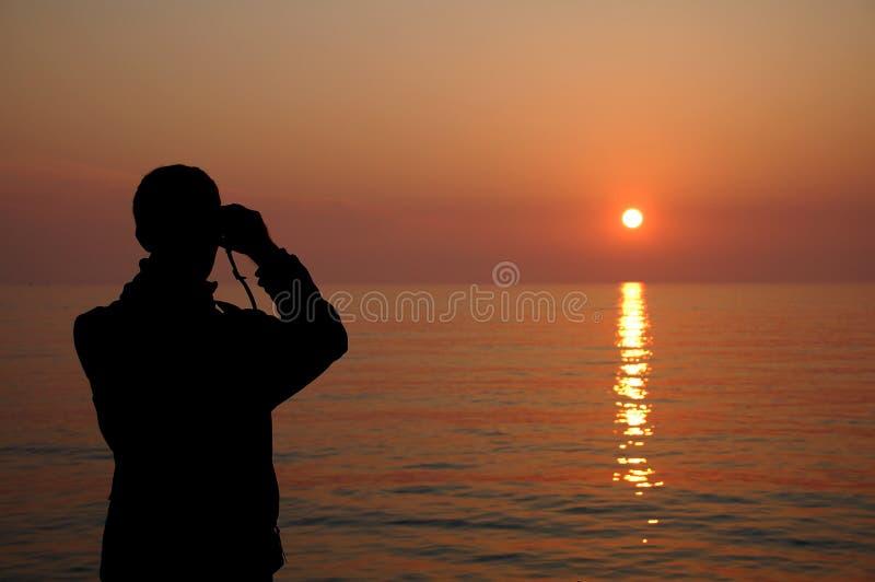 观看与双筒望远镜的一个人的剪影日落 免版税库存照片