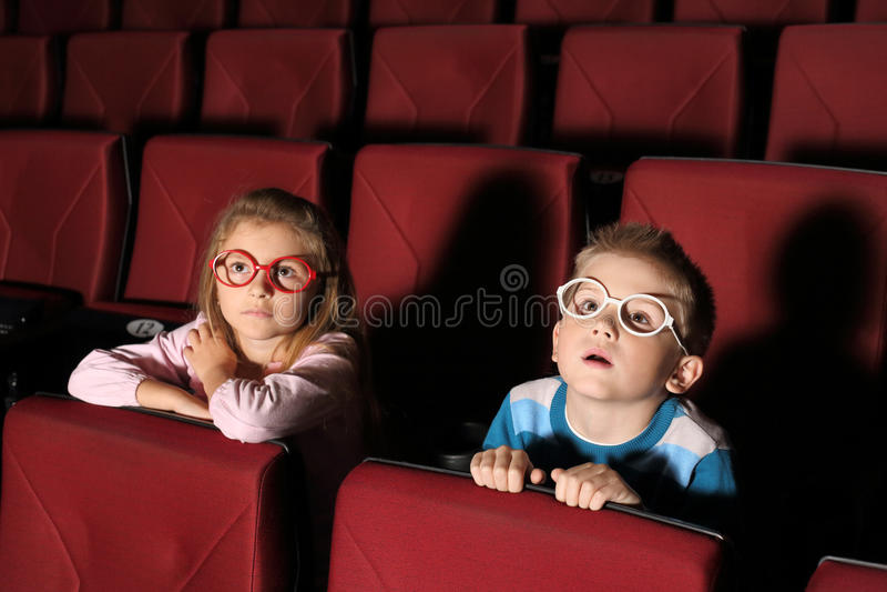 观看与兴趣的小男孩和女孩一部电影 免版税图库摄影