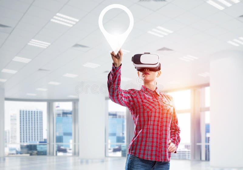 观看与VR设备在盘区和工作对此的女孩 混合画法 免版税图库摄影