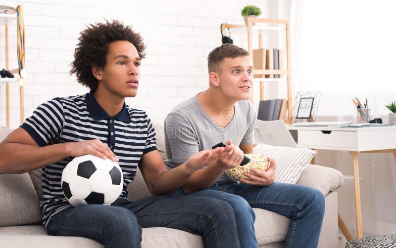 观看世界与球的朋友橄榄球冠军在沙发 免版税库存图片