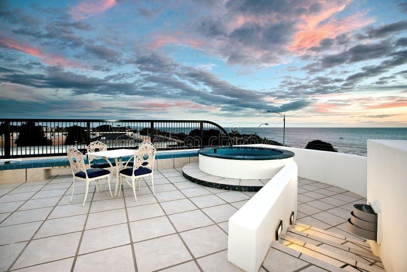 观看云彩从您的私有极可意浴缸滚动在屋顶!! 库存照片