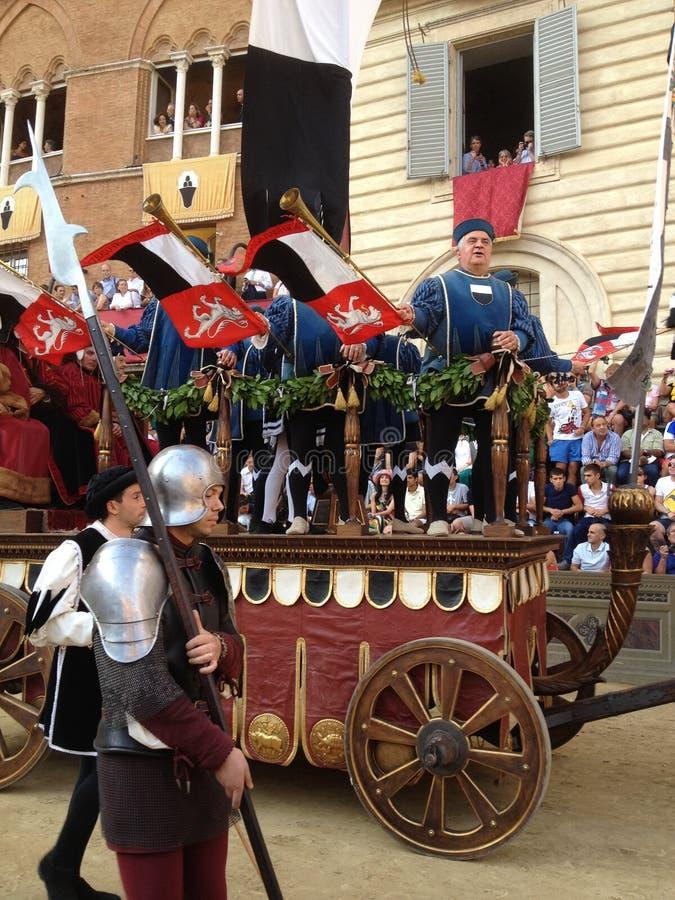 观看五颜六色和花梢传统服装的游人游行在跑马, Palio二锡耶纳,举行在中世纪正方形 免版税库存图片
