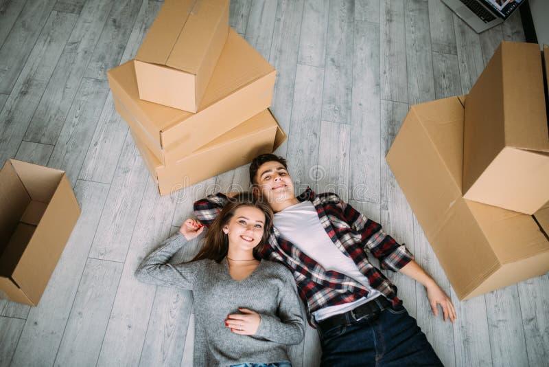 观看从上面,看照相机说谎在他们新的家地板上的一对年轻夫妇  免版税库存照片