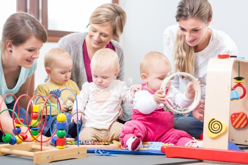 观看他们的婴孩的三个愉快的母亲使用与安全多彩多姿的玩具 免版税库存图片