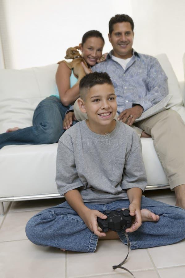 观看儿子的父母打在客厅正面图的电子游戏 库存照片