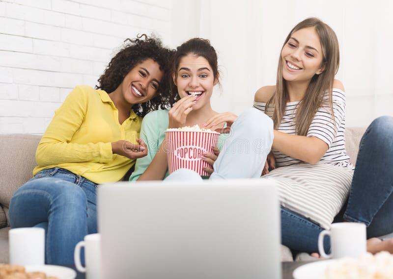 观看喜剧电影和在家吃玉米花的女孩 免版税图库摄影