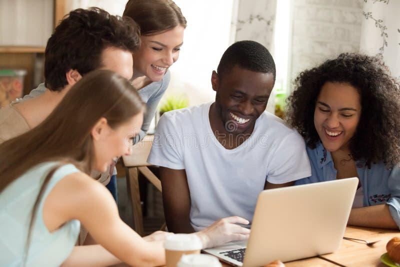 观看喜剧电影的不同的学生坐在书桌在屋子里 库存图片