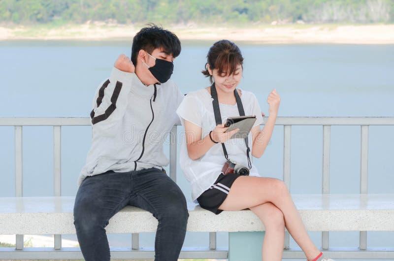 观看在人脉的快乐的最好的朋友搞笑照片通过智能手机 免版税库存图片
