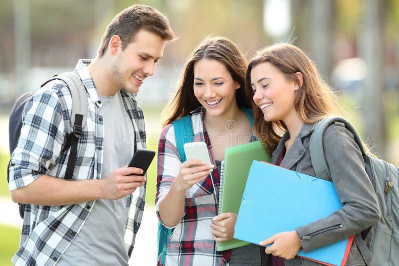 观看在他们的智能手机的学生媒介 图库摄影