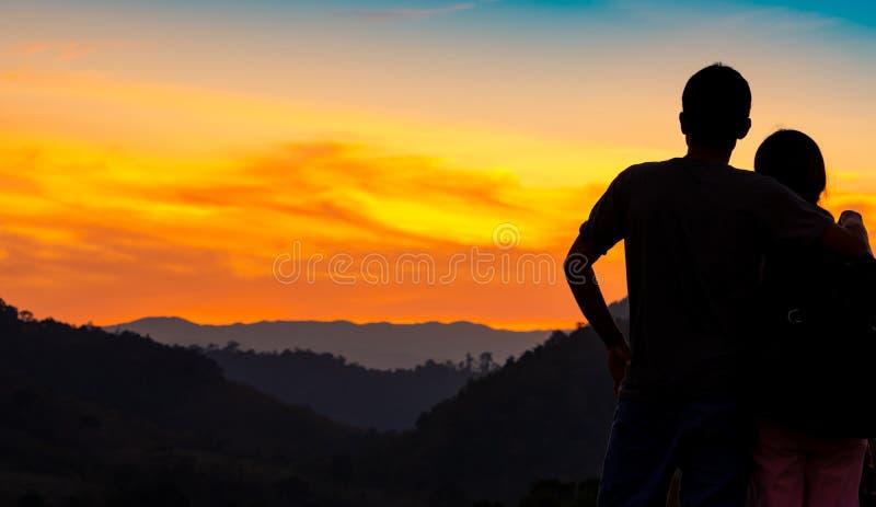 观看在山层数的浪漫夫妇后面看法美好的日落 夫妇旅行 背包徒步旅行者愉快在爱和旅行 免版税库存照片