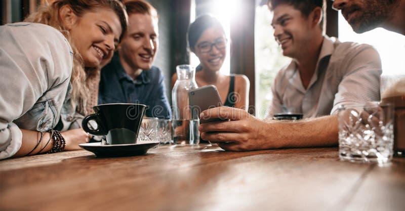 观看在手机的年轻朋友照片 免版税库存图片