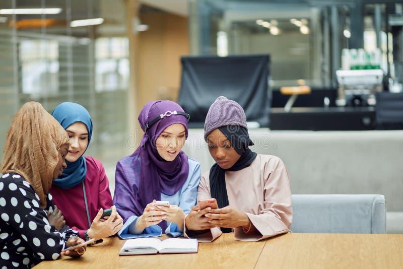 观看在手机音乐录象剪辑的阿拉伯年轻女人一起站立 图库摄影