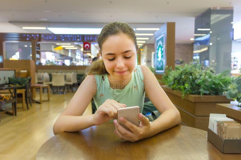 观看在智能手机的年轻美丽的青少年的女孩滑稽的录影在咖啡馆 免版税库存图片