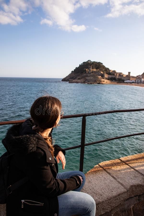 观看在海岸的中世纪堡垒的妇女靠近地中海镇 库存照片