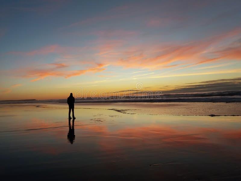 观看在海滩的孤独的人日落 免版税图库摄影