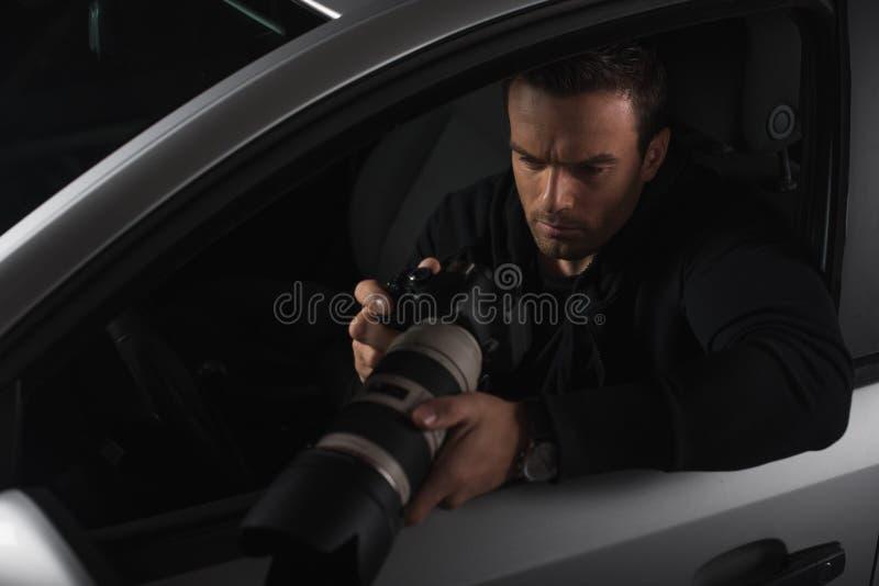 观看在照相机的照片与接物镜和做监视从的无固定职业的摄影师 图库摄影