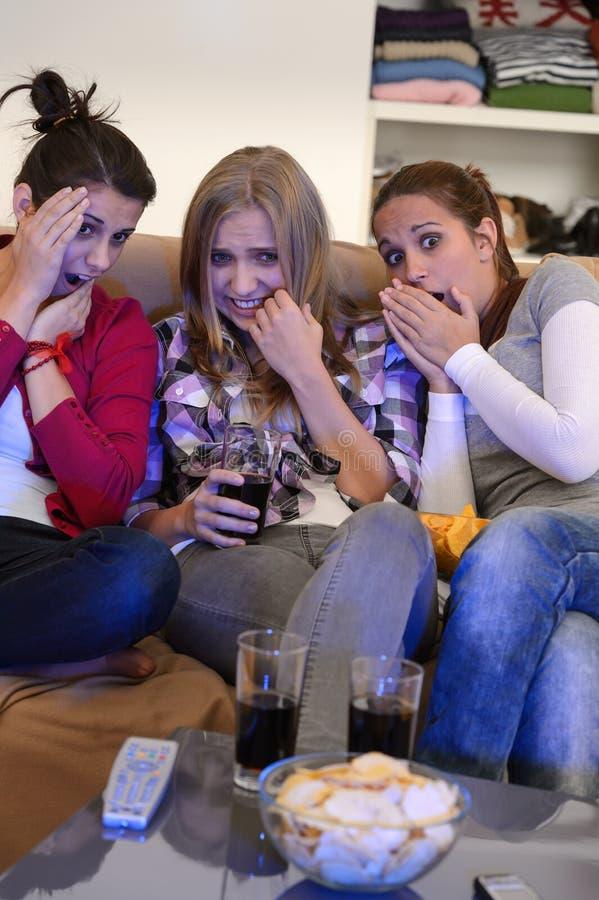 观看在电视上的害怕的女孩恐怖片 图库摄影
