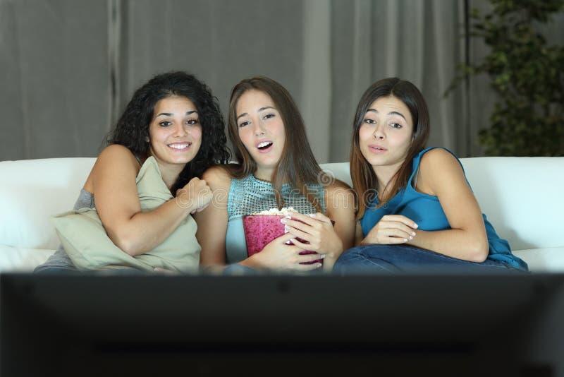 观看在电视的三个朋友浪漫电影 免版税库存照片