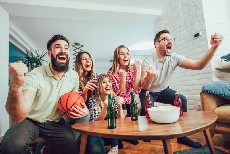 观看在电视的愉快的朋友或蓝球迷篮球比赛 库存照片