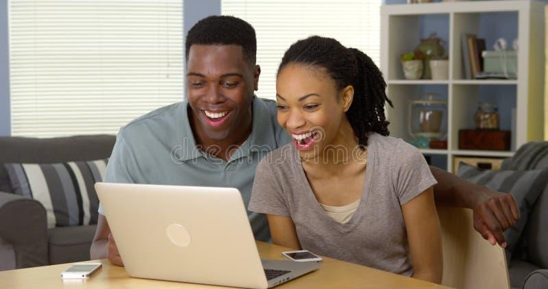 观看在膝上型计算机的年轻黑夫妇滑稽的录影 免版税库存图片